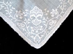 Detail, fichu, mid 18th century. Very fine muslin embroidered with fine whitework flowers and leaves all along the edge.
