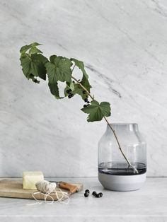 Grey minimalistic vase from Muuto by designer Thomas Bentzen.Representing the interplay of light and heavy, the Elevated Vase is a study of Scandinavian contrasts. The bottom is made of ash wood while the body is translucent mouth-blown glass. The vase wo