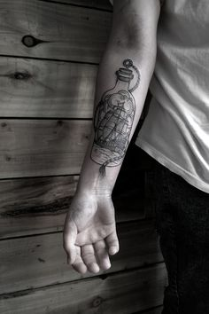 Black ship in a bottle arm tattoo.