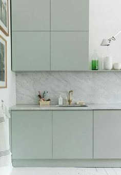 pale green kitchens - Emma Persson Lagerberg's pale green Swedish kitchen with white-painted floor and marble backsplash - bloesem via Atticmag