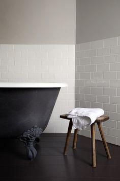 Dark floorboards in bath/basin area with Matt black bath. White subway wall tiles in wet area.