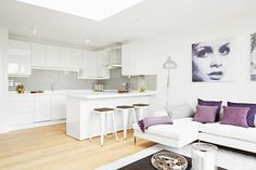 Glendon Apartments by QNEWHOMES LTD Bespoke open plan kitchen / living room, glass splashbacks, corian worktops, oak floors.