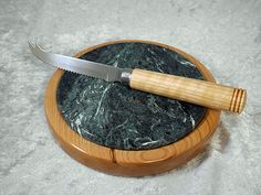 "7"" cheese board and matching stainless knife turned from cherry.  The 6"" diameter center tile is green marble."