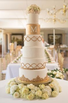 White and gold classic wedding cake with a floral base || Sydney Gibson & Kyle Matusoff of Hot Springs
