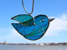Blue - green songbird is a beautiful streaked glass with an iridescent turquoise green wing. This is my original design and came from my love of listening to the songs outside my kitchen window. The wire detailing adds beauty and strength to the suncatcher. The streaky detail will be different on each bird- some of the glass will look dark before you hang it in a window--to bring it to life with light.  This measures 5.5 x 3 and comes with a suction cup.  Stained glass suncatchers are…