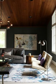 Dark walls, wooden ceiling, the Barcelona chairs and the purple cushions