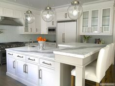 Amazing kitchen features three clear glass globe pendants illuminating a white center island topped with statuary marble fitted with a small corner prep sink and gooseneck faucet. The kitchen island is fitted with an L shaped breakfast bar topped with statuary marble lined with ivory upholstered barstools. A stainless steel kitchen hood stands over  a Viking Range. Shaker kitchen cabinets are paired with black countertops and a blue glass tile backsplash laid out in brick pattern