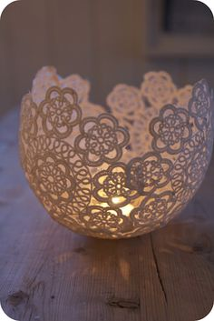 Hang a blown up balloon from a string. Dip lace doilies in wallpaper glue and wrap on balloon. Once they're dry, pop the balloon and add a tea light candle. Great centerpiece idea on burlap runner :)