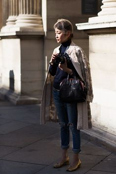 #sartorialist ivory quilted jacket with distressed jeans, navy top, birdcage hat/veil, gold low heeled shoes