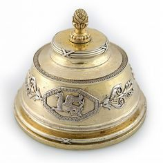A GILDED SILVER EMPIRE REVIVAL STYLE BOX WITH COVER, FABERGE, MOSCOW, 1899-1908. Of tapering cylindrical form, the main body decorated with applied silver embellishments featuring griffins in octagonal frames surrounded by palmettes, the cover topped with a pinecone finial, the cap further decorated with ribbon-tied band, the base of the cover with a wreath of chased laurel leaves.