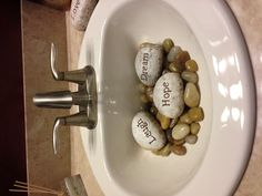 Neat way to cover an unsightly drain. Fill a guest sink partially with smooth stones (large enough not to fall into the drain) and message rocks.