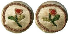 Buttons; a pair of 18th century ivory silk waistcoat buttons embroidered in coloured threads with a rose stem within a mushroom coloured circular border, 0.75in diameter;