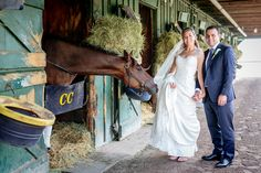 Saratoga Race Track wedding and the bride and groom pose with a horse on the backstretch | wedding horses