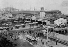 The original Ferry Building. This snub-towered ferry building stood a short distance to the north of its well-known descendant. When the picture was taken in 1886 most cars were cable cars, but a few horse-drawn ones remained. The first ferry sheds were built in 1877.