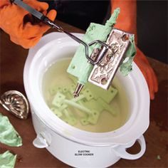 strip paint of hardware with hot water bath. fill a slow cooker with water and set the dial to high. The heat and moisture will soften the paint, and often it will fall off as a single piece.