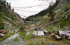 Logging Camp, Kham - 20x200 This tent is the home of a small community of hardscrabble loggers who live on this holy mountain. Tibetans consider the sources of rivers to be holy places and decorate them accordingly. The loggers tend to the prayer flags and serve tea to pilgrims. They cut trees when necessary and sell them to Chinese truckers who bring them back down to the mainland.