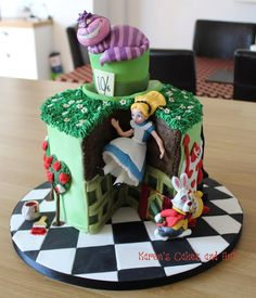 Alice falling into Wonderland cake. Cheshire Cat, Mad Hatter's hat, playing cards, white rabbit, checkerboard effect. https://www.facebook.com/karenscakesandart