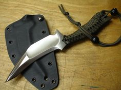 Migs ST by DJ Urbanovsky owner of American Kami. OVERALL LENGTH: 10.5 Inches BLADE LENGTH: 5.0 Inches BLADE THICKNESS: 0.25 Inch STEEL: 1095, Differentially heat treated GRIND: Hollow right hand chisel EDGE: Standard chisel HANDLE: Paracord SHEATH: 0.08 Inch thick Kydex with drain hole