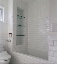 Tile shower shelves at end of bathtub. Large shelves. Subway tile. Glass shelves.