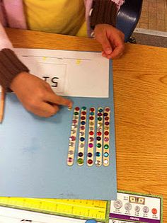 Place Value with sequins and popsicle sticks.  Everyone loves a little bling! :)