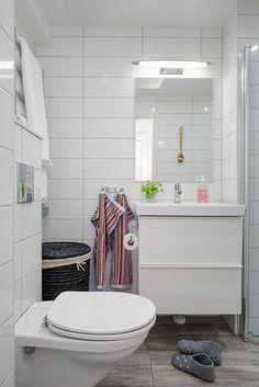 Biała łazienka z podłogą imitującą drewno