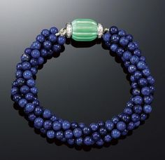 CARTIER LAPIS LAZULI, TURQUOISE AND DIAMOND BRACELET, 1920S. Designed as four rows of lapis lazuli beads to a fluted barrel-shaped turquoise clasp embellished with single-cut diamond rondelles, length approximately 210mm, accompanied by a case from Cartier Paris.