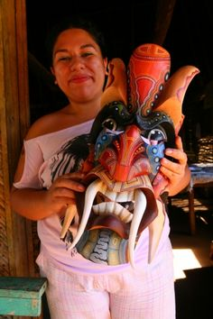 Boruca masks A Boruca craftswoman holds up a colorful carved mask with large tusklike teeth.