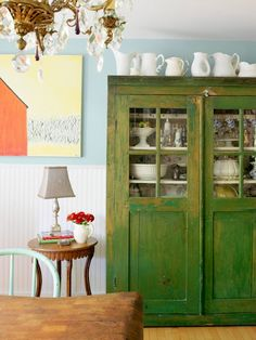 i like the collection of pitchers at the top!  plus very cute distressed armoire.