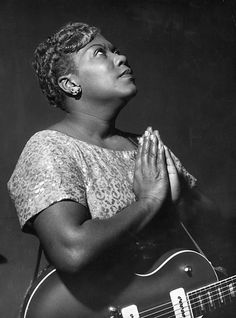 Sister Rosetta Tharpe poses in prayer with an electric guitar during a concert with Chris Barber's jazz band in Cardiff, Wales, 1957.