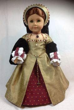 Here is an 7 piece Tudor gown outfit which has been designed to fit popular 18 inch dolls. If you would like measurements to see if it will fit your doll please contact me. The outfit consists A gown made using a gold colour silk dupion fabric with black cotton velvet sleeves, it is fully lined and is decorated with pearl effect beads and red gems all sewn on by hand, the gown fastens at the back with clear snaps. A pair of brocade type fabric removable fore sleeves, decorated with red…