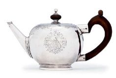 A GEORGE I SILVER TEAPOT MARK OF AUGUSTINE COURTAULD, LONDON,  the first of the Huguenot Courtaulds  who came to London  Made 1726 Bullet shaped and on a short collet foot, with a carved wood spout and a tapering spout, the hinged cover with a part turned wood finial, engraved at the shoulder and on the cover with foliage scrolls, engraved with a coat-of-arms