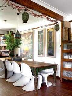 Vintage and modern mix: farmhouse table, modern chairs, interesting art, interesting lighting.