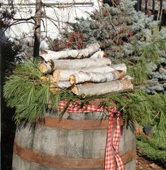 Berch Logs & Pine Branches Resting on a Vintage Wine Barrel