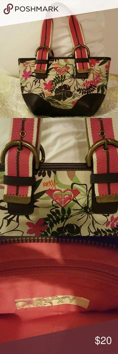 Cute Roxy handbag Classic Roxy print on this canvas & leather handbag. Pink, tan, brown & green predominant. Belt & antique brass buckle handles. Super durable. Clean & in great shape, inside & out. Roxy Bags