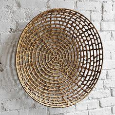 Shallow basket on wall. Baskets abound at thrift stores. A lot of them are perfect for walls. Adds natural texture and round shape-wreath alternative-very inexpensively.