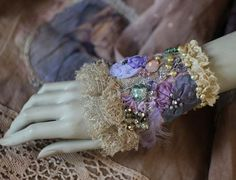 Delicate bold wrist wrap/cuff is made of lovely vintage textiles- base is vintage golden lame fabric with purple silk thread. The cuff is adorned with satin and tulle sculpted blooms, hand stitches with mohair threads, beaded with freshwater pearls and bold clear seed beads. The upper edge is trimmed with very delicate antique Valenciennes lace ruffles, the bottom edge with oatmeal shade couture lace trim. Fastens with mauve tulle ribbon, adjustable size. Measurements : 18x14 cm ( 7,1x 5...