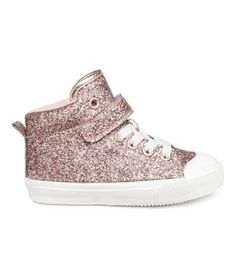 Pink/glittery. High tops in shimmering faux leather with a lightly padded edge, hook-loop tab fastener, elastic laces, and a loop at back. Mesh lining and