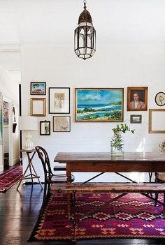 Dining room - white walls, dark wood floors, rustic wood table, bright colorful rug, gallery wall
