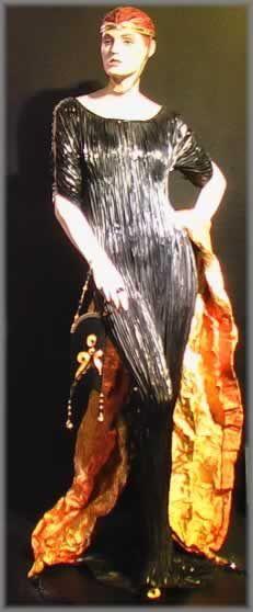 Hijo del pintor del mismo nombre, Mariano Fortuny, nacido en Granada en 1871, pero instalado en Venecia desde su juventud, irradio a toda Europa una estética refinada, rupturista y vanguardista, de la que es emblema el modelo Delfos, que marca decisivamente la evolución de la moda femenina, al liberarla de corsés y demás atributos opresores. Se cuenta que este vestido de seda plisada y sin costuras nació de la fascinación que su esposa Henriette sentía ante ña contemplación del famoso Auriga…