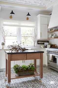 Make the most of a kitchen by adding a rolling kitchen cart, open shelving, and a charismatic tiled floor. White cabinets and large windows allow natural light to brighten and open all the possibilities of any space. // Featured Design: Ella™ from Cambria's Marble Collection™