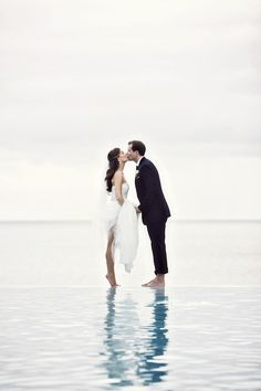 Beach wedding photo- My mom will kill me if I get in the water with my dress on...  But it's so cute