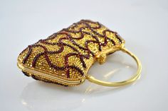 This exquisite hand crafted Swarovski Crystal clutch has been adorned in a multitude of Gold Topaz and Dark Burgundy Red crystals that have been applied in a coordinating geometirc swirl pattern. There are over 4500 crystals that have been hand applied to this clutch in a 3D raised pattern and finished with a gold topaz metal chain and solid hand frame. The pictures do not do this item justice!  Details & Fit  • Patterned Rectangular Clutch Bag • Metal hard case • Crystal embellished bod...
