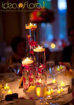 Hermoso centro de mesa de trío de cilindros de cristal. Con orquídeas y velas flotantes.