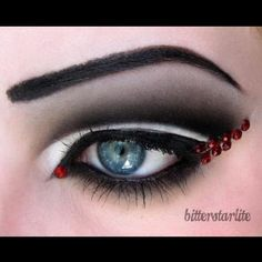 Dramatic black and white smokey eye makeup with red crystal accents.