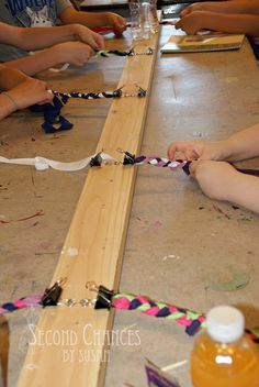 I love this set up w/binder clips on a 2x4 for friendship bracelets! Camp crafts ftw!
