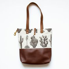 Large natural linen tote with brown leather straps and bottom  Screen printed with non-toxic black ink  Lined with 100% cotton canvas  Inside