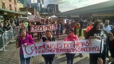"""""""Decolonize,"""" """"Columbus is no hero!! Fighting terrorism since 1492""""  Source: Does anyone know who took this picture, or when it occurred?"""
