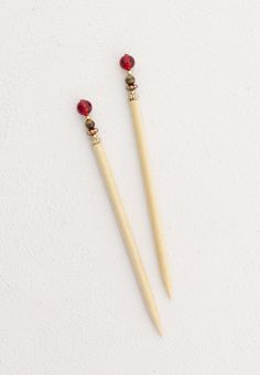 "Ruby Red and Goldstone beads with accents of black nickel and gold delight the top of this set of 5"" blonde hair sticks. A heart's delight!"