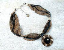 Collana in pelle e tessuto nera e bronzo