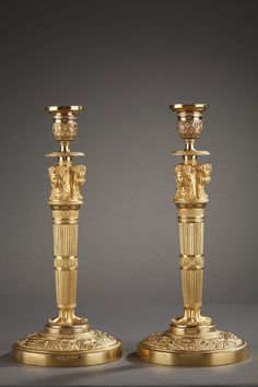 An exceptional pair of Empire candlesticks decorated with three female busts, veiled and crowned with flowers, resting on a fluted barrel, very finely chiselled with flowers in crosspieces a